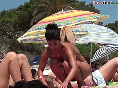 Topless brunette friends with nice tits on the beach