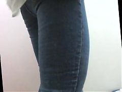 hot girl in tight jeans peeing in toilet - side view